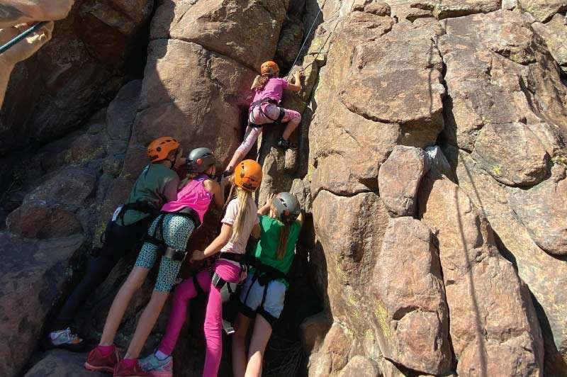 Children Learning to Rock Climb